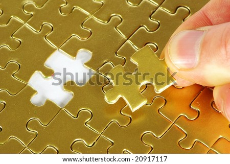 hand holding a puzzle piece - stock photo
