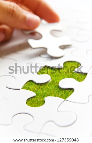 hand holding a puzzle piece, green space concept