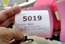 Hand holding a queue number ticket for a counter service at a bank while waiting turn to be attended to. A queue ticket showing the current waiting number been assigned.