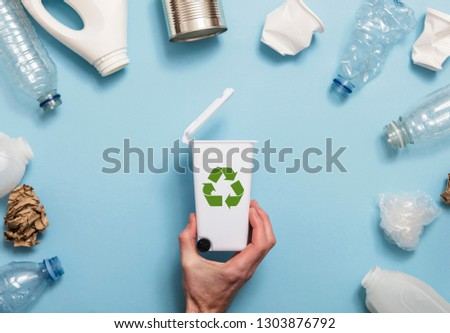 Hand holding a recycling garbage bin with lots of waste packaging #1303876792