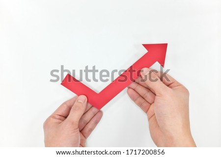 Hand holding a red arrow going up. Economy and stock market bounce back and recovery concept.  Stockfoto ©