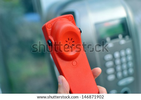 Hand holding a red handset of a public telephone