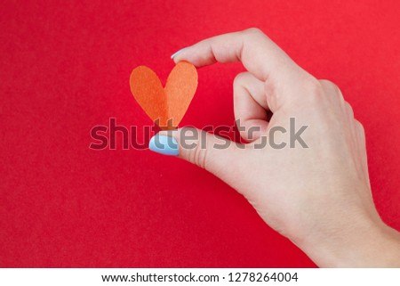 hand holding a red heart on a red background. Background for Valentine's day #1278264004