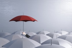 Hand holding a red umbrella on top of other white umbrellas. Business and safety concept