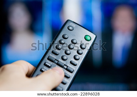 Hand holding a remote control pointing to a blurred TV program