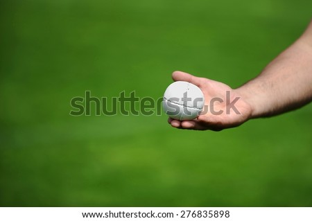 Hand holding a rounders ball. Rounders is a bat and ball game between two team that involves hitting a hard leather cased ball with a wooden bat.