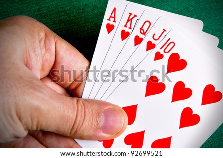 Hand holding a Royal Flush poker card sequence