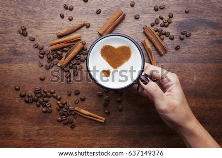 Hand holding a rustic white mug with coffee cream. Food art creative concept image, Heart shapes drawing with cinnamon powder over wooden background. #637149376
