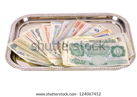 hand holding a silver tray with a selection of now antique monetary banknotes from a variety of countries, isolated to white
