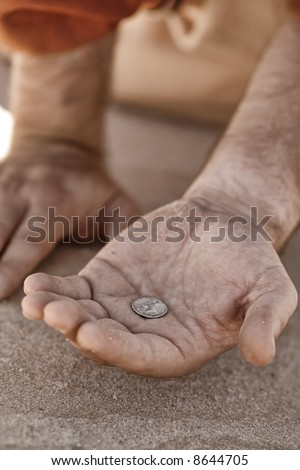 Hand holding a single coin - beggar, destitute, donation, charity, good samaritan, etc,  Closeup with shallow dof. - stock photo