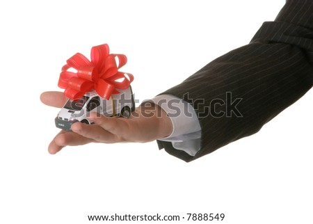 Hand holding a small car with ribbon isolated on pure white.