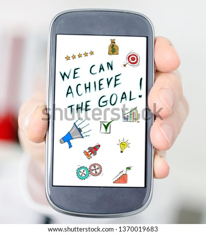 Hand holding a smartphone with goal achievement concept #1370019683