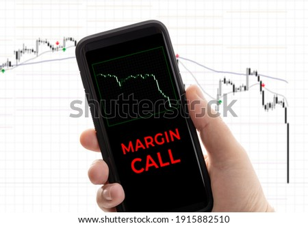 Hand holding a smartphone with the message margin call. Trading loss stock exchange. Brokerage account ストックフォト ©