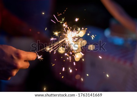Hand holding a sparkler during blue hour in the backyard at a family celebration
