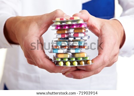 Hand holding a stack of many different pills