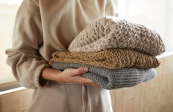 Hand holding a stack of sustainable cloths in tracksuit, homemade and Eco friendly fabric