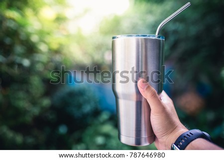 Hand holding a stainless steel tumbler / keeping the temperature of the drink cold or hot with copy space
