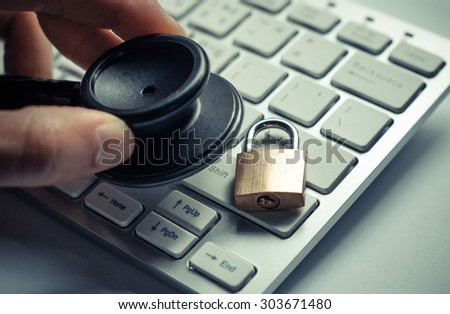 hand holding  a stethoscope over computer keyboard with a security lock - computer system check and maintenance concept