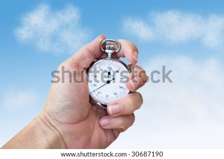 Hand holding a stop watch or production watch in a blue sky