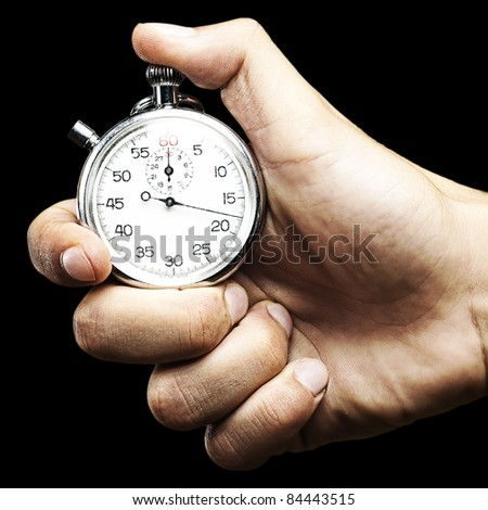 hand holding a stopwatch against a black background