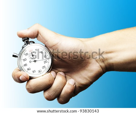 hand holding a stopwatch against a blue background