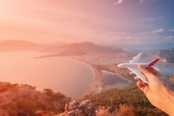 Hand holding a toy airplane on the background of the sea beach and lagoon at sunset. Concept of opening new flights in airlines and air transport