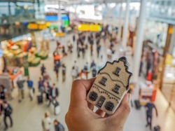 Hand holding a traditional Dutch house in Delft blue porcelain in Schiphol airport in the Netherlands.