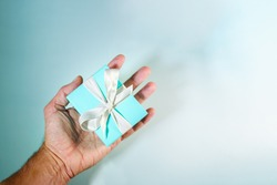 hand holding a turquoise gift boxe tied with white silk ribbon. Suitable for concepts like luxury gift, anniversary, Valentine's day, Mother's day or christmas. Copy space available