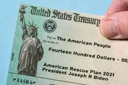 Hand holding a US Treasury illustrative check to illustrate American Rescue Plan Act of 2021 payment on blue background