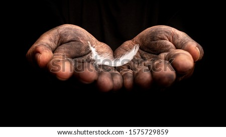 Hand holding a white feather on dark background. Do bad things to protect good thing. Conceptual art photography.  #1575729859