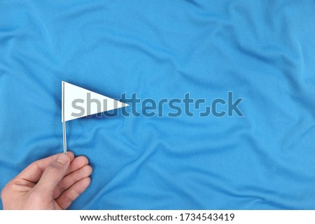 Hand holding a white flag in blue background. Peace, ceasefire, surrender and truce concept.
