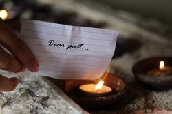 Hand holding a white note paper written - Dear past. Burning it on a burning candle in a ceramic bowl. Hope and new life concept.