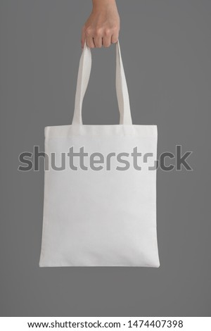 Hand holding a white tote bag canvas fabric on grey background