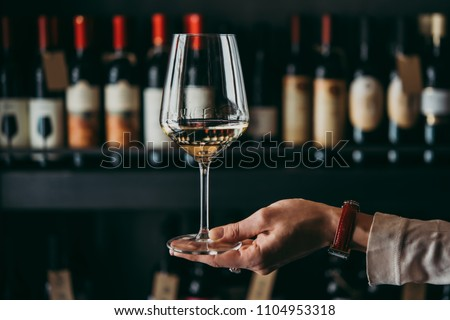 Hand holding a wine glass. #1104953318