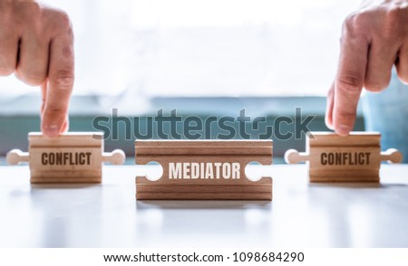 Hand holding a wooden jigsaw puzzle with conflict and Mediator word. There is a matching puzzle next to it. The concept of solving problems, all problems can be solved, connection.