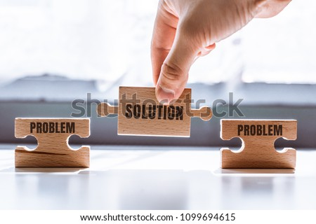 Hand holding a wooden jigsaw puzzle with solution and problem word. There is a matching puzzle next to it. The concept of solving problems, all problems can be solved, connection. #1099694615