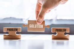 Hand holding a wooden puzzle with the word solution. There is a matching puzzle next to it with the word problem. The concept of solving problems, all problems can be solved.
