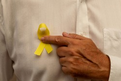 Hand holding a yellow ribbon. Yellow may