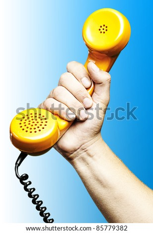 hand holding a yellow vintage telephone over blue background