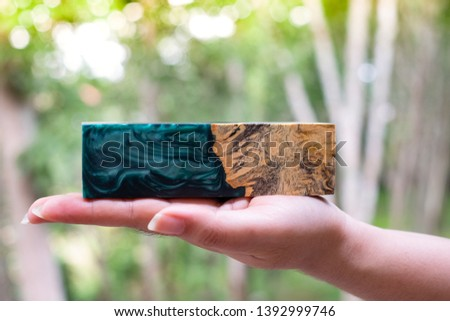 Hand holding Afzelia burl wood bar casting with epoxy resin Stabilizing for blanks on bokeh abstract background