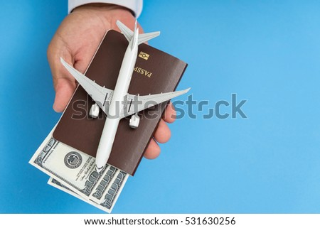 hand holding airplane model, money banknote and passport on blue desk background ,Airline Ticket Booking, Travel holiday Concept, copy space on Right side. - Shutterstock ID 531630256