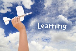 Hand holding airplane model on blue sky and Learning text