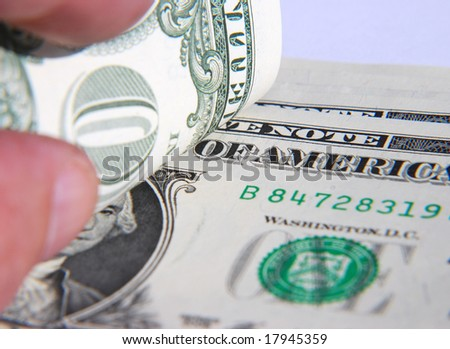 Hand holding American dollar notes - focused on writing