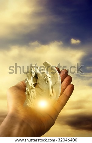 hand holding an angel with divine light