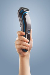 hand holding an electric hair clipper on a blue background