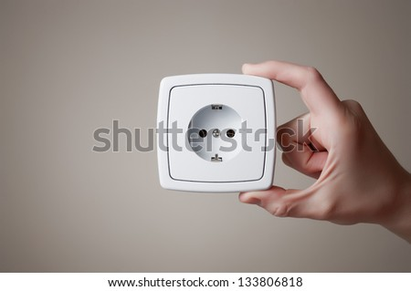 Hand holding an electric outlet