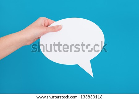 Hand holding an empty speech bubble on blue background.