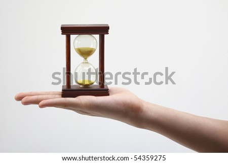hand holding an hour glass on the plin background