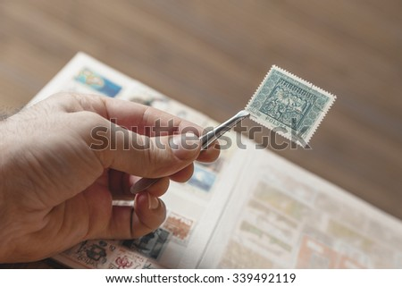 Hand holding an old Polish post stamp