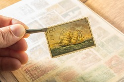 Hand holding an old Yugoslavian post stamp
